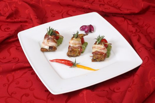 Rolls with bacon and fresh vegetables on a white plate