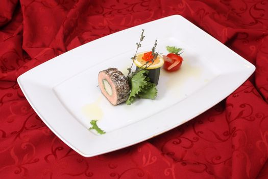 Stuffed fish with vegetables on white plate