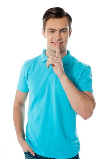 Silence gesture by a young guy wearing blue t-shirt against white background