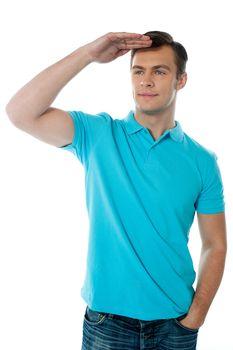 Cool young chap posing with hand on his head, seeking far far away
