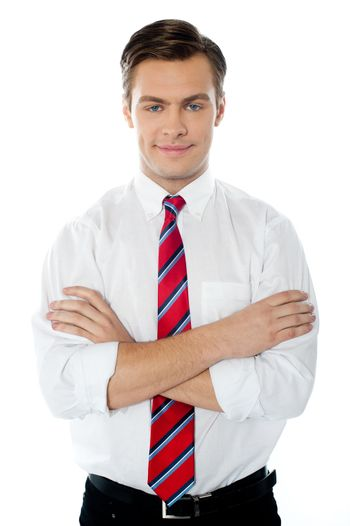 Cute young professional male standing with folded arms against white background