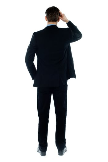 Back-pose of a corporate person thinking hard isolated over white background