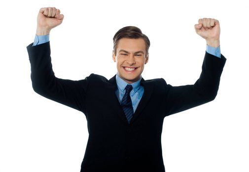 Portrait of confident young businessman celebrating success with arms up