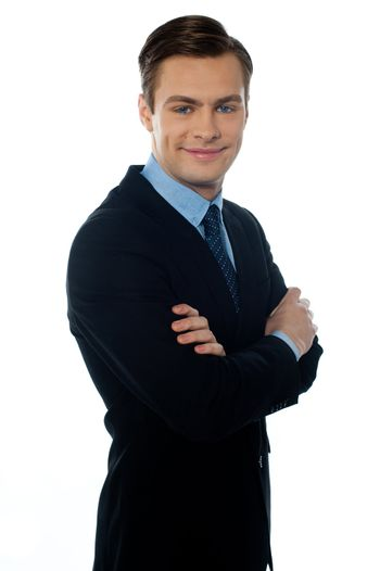 Young successful businessman posing folded arms over white background