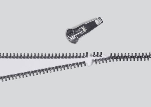 symbolic studio photography of a damaged zipper in light back, seen from above