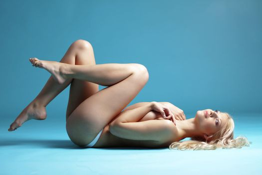 Portrait of very beautiful naked woman over blue