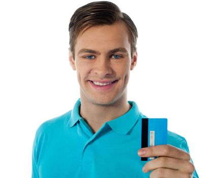 Fashionable young guy posing with debit card against white background