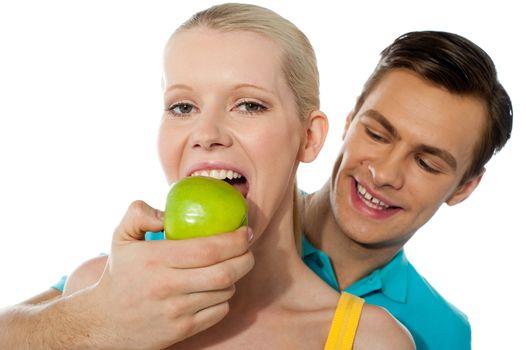 Boyfriend making her partner eat an apple. Love couple