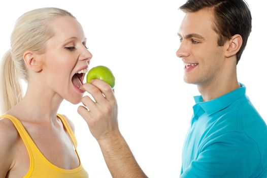 Young guy making her pretty girlfriend eat an apple. Healthy couple
