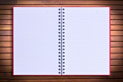 red notebook on wood background