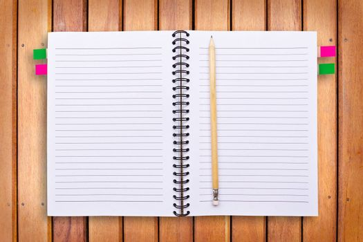notebook and pencil on wood background