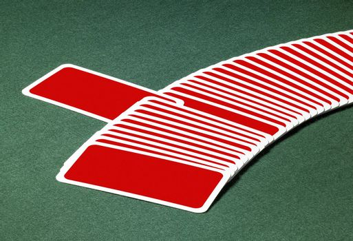 studio photography of spread out playing cards with one chosen, located on green felt