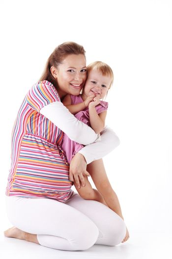 Pregnant mother with her small daughter studio shot