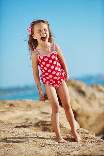 Cute child wearing swimsuit playing at beach in summer