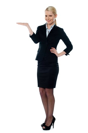 Full shot of female executive posing with open plam isolated over white background