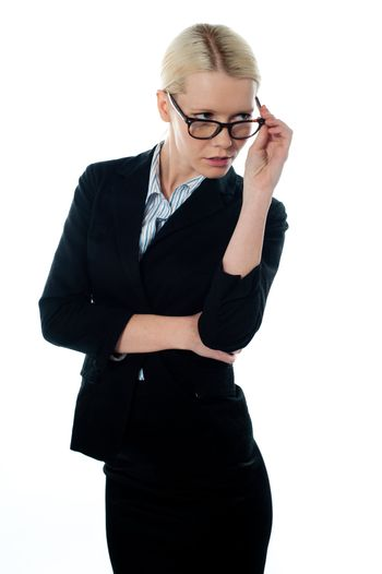 Full view of attractive businesswoman looking away from beneath her glasses