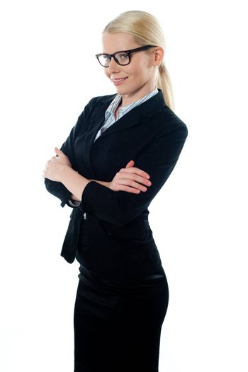 Side view of pretty young female executive posing with arms crossed