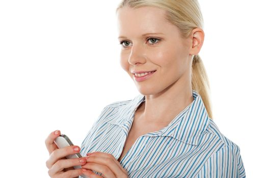 Beautiful corporate female using cellphone, smiling and looking away