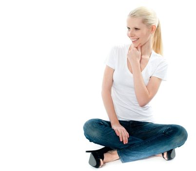 Pretty girl in white top and blue jeans sitting on floor, mischievious smile on face