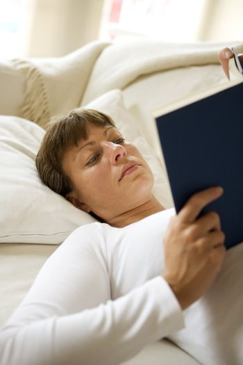 Woman in the sofa reading a book