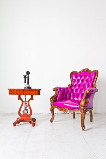 vintage purple luxury armchair and telephone in white room