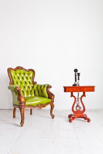 vintage luxury armchair and telephone in white room