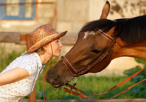 Woman in hat and horse face to face. Close-up portrate