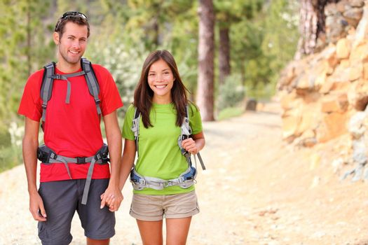 Hiking. Hiker couple portrait. Hikers walking in forest during camping travel hike. Healthy lifestyle photo of Asian woman and Caucasian man holding hands.
