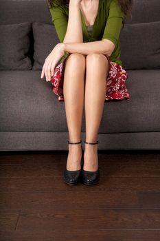 minimal heeled black shoes sitting on sofa