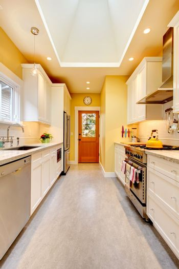 Yellow kitchen with white cabinets and stove.