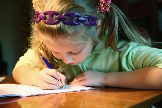 An image of a little girl doing her homework