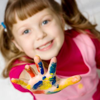 An image of a little girl with her hand in paint