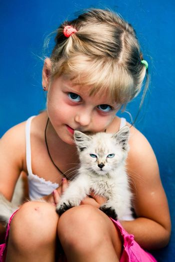 Smiling girl with a small kitten in her arms