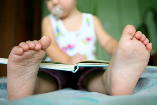 An image of a baby girl reading a book