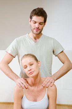 man massaging woman's shoulders