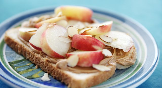 open-faced sandwich with peanut butter, fresh white peach slices and sliced almonds