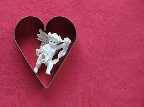 heart-shaped cookie cutter with a figure of cupid inside