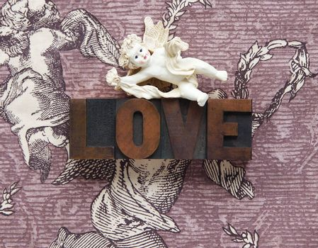 a cupid figure atop the word love in wood type