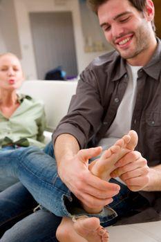 man massaging woman's feet