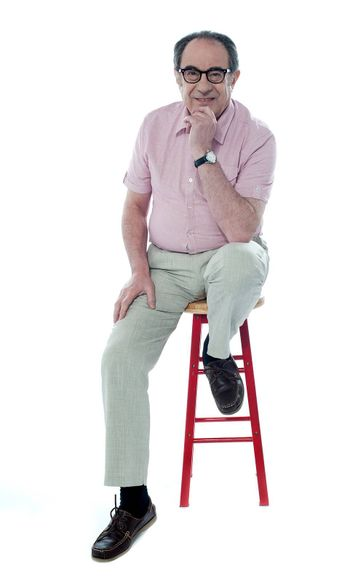 Confident senior man looking at you as he rests on stool, studio shot