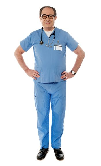 Full length view of smiling experienced medical professional posing hands are on his waist