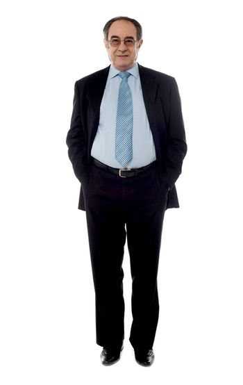 Company manager wearing black suit standing in front of camera with hands in pocket
