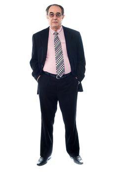 Senior executive ewearing eyeglasses and posing with hands in pocket