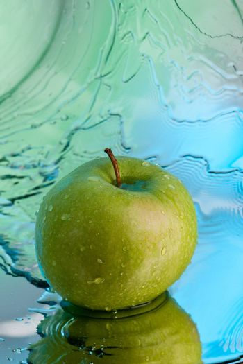 ripe green apple over abstarct blue background