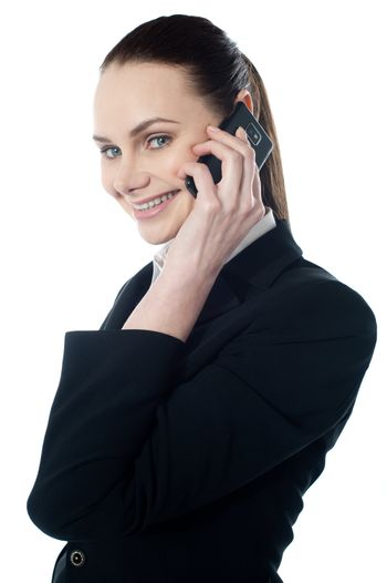 Female executive talking on mobile and smiling at camera