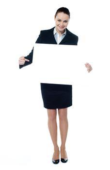Female representative pointing towards placard, smiling at camera