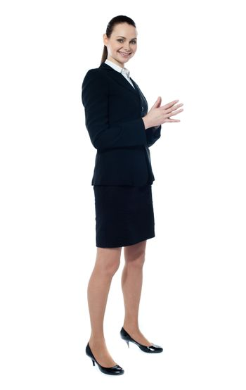 Full length of corporate smiling woman posing in style against white background