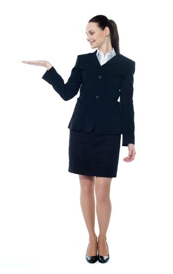 Full-length pose of young feamle ceo showing and presenting copyspace in business