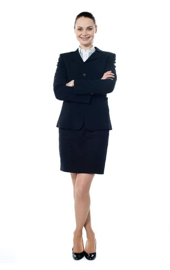 Smiling successful businesswoman posing with folded-arms and crossed legs