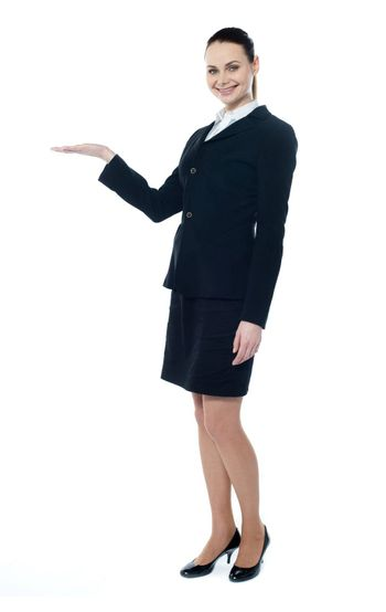 Full length of beautiful business woman showing copyspace up over white background
